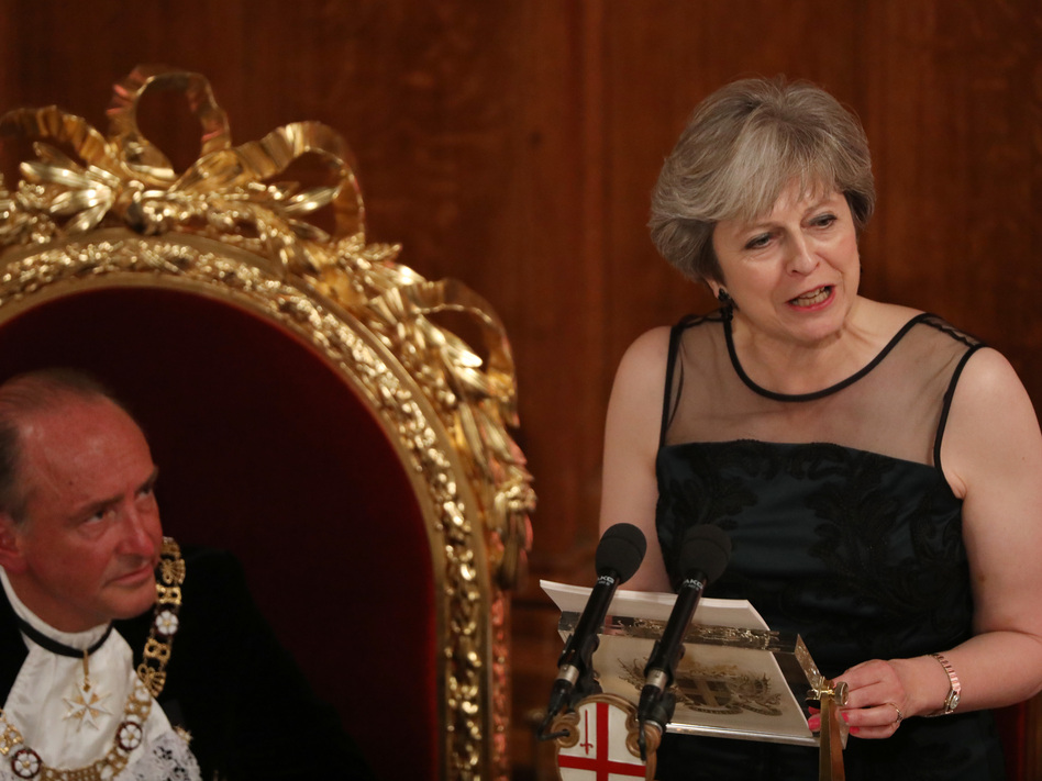 U.K. Prime Minister Theresa May speaks as Charles Bowman, Lord Mayor of the City of London, listens during the annual Lord Mayor's Banquet at the Guildhall, in the square mile financial district of the City of London on Monday. (Bloomberg/Bloomberg via Getty Images)