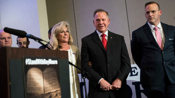 Alabama GOP Senate nominee Roy Moore listens to a question during a news conference with supporters and faith leaders along with his wife, Kayla, on Thursday in Birmingham.