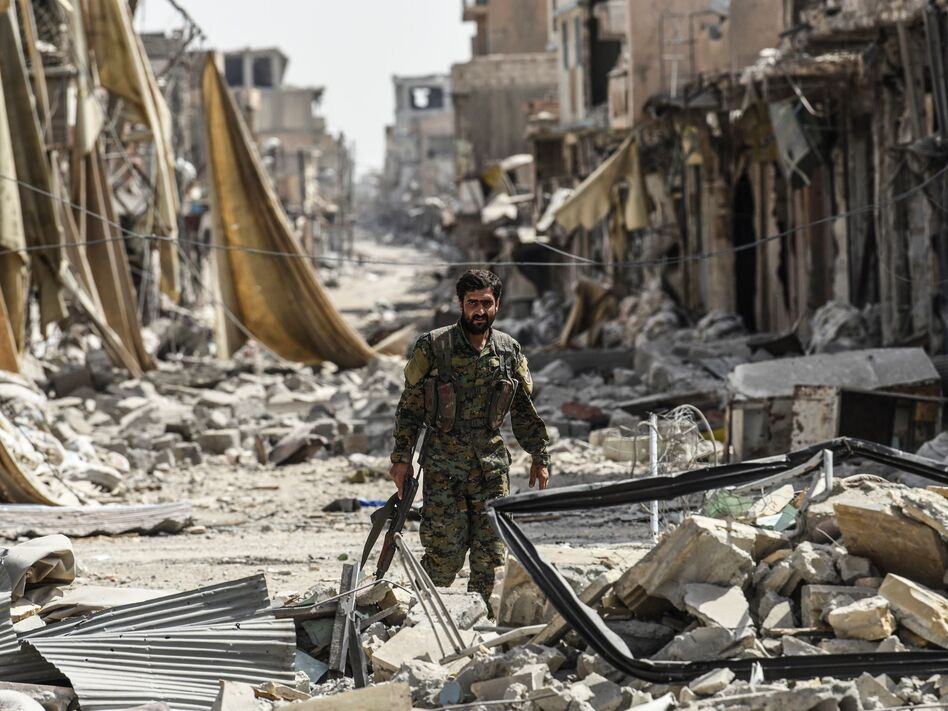 A member of the Syrian Democratic Forces, a group allied with the United States, walks through debris in Raqqa, Syria, formerly the de facto capital of Islamic State. (Bulent Kilic/AFP/Getty Images)