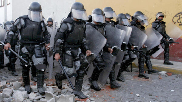 Policemen charge on protesters in San Salvador Atenco, Mexico, in May 2006, in efforts to reestablish order in the city. Two people died and many were abused in the battle that broke out when police attempted to remove peddlers from the city and neighboring Texcoco.