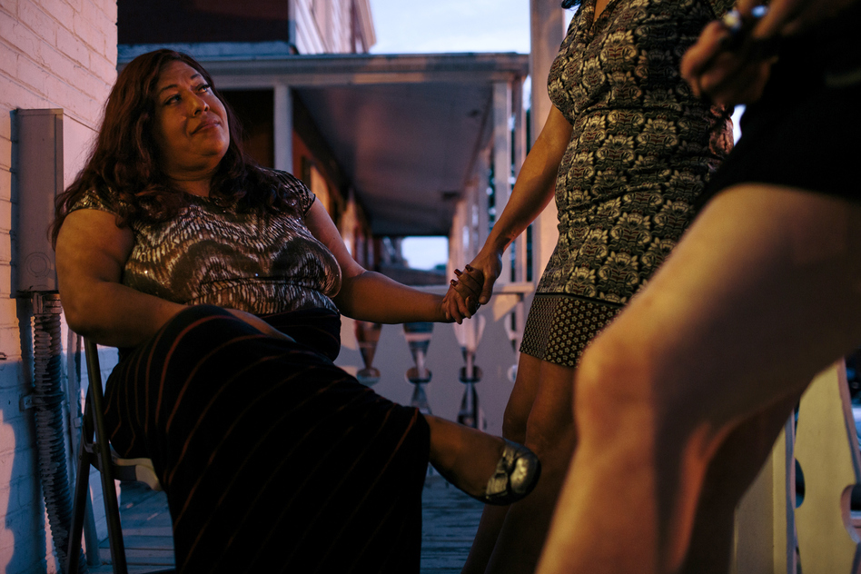Ruby Corado (left) with her friend and Casa Ruby board member Consuella Lopez on the porch of one of the transitional group homes Corado runs in Washington, D.C., in 2015. (Lexey Swall/GRAIN for NPR)