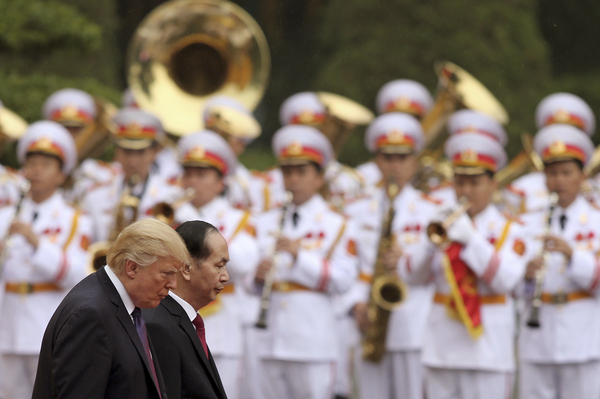 Three members of the White House Communications Agency have been reassigned after allegations of improper behavior on a recent presidential visit to Vietnam. President Trump, seen here with Vietnamese President Tran Dai Quang at the Presidential Palace in Hanoi.