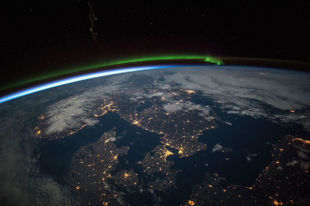 astronauts aboard the space station took this image of southern scandinavia lit up at night a green aurora is visible over the horizon