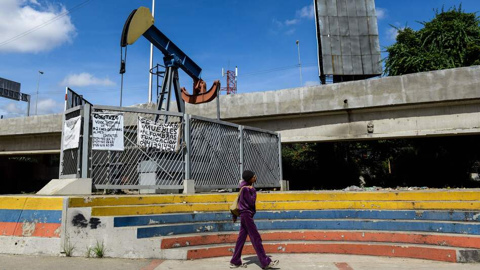 A woman walks past an oil pump in Caracas earlier this month. Part of Venezuela's fiscal woes arises from lowered gas prices worldwide — a huge hit to an economy so reliant on its oil production.