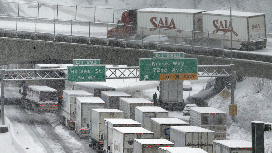Early-morning traffic backs up on Interstate 5 during a Jan. 11 snowstorm in Portland, Ore. Truck drivers say such conditions, combined with limitations on their working hours, cost them a lot of money because of their mileage-based pay. (Don Ryan/AP)