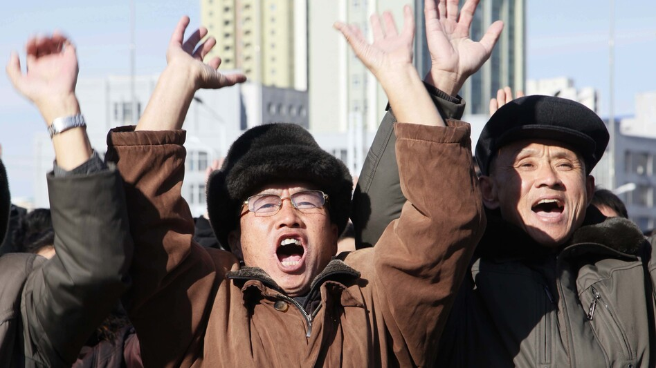 People at the Pyongyang Train Station in North Korea cheer as they watch the news broadcast announcing leader Kim Jong Un's order to test-fire the newly developed inter-continental ballistic missile Hwasong-15. (Jon Chol Jin/AP)