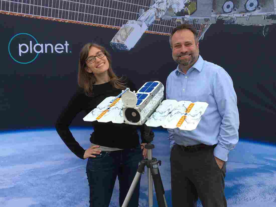Stacey Vanek Smith and Robert Smith with a model satellite.