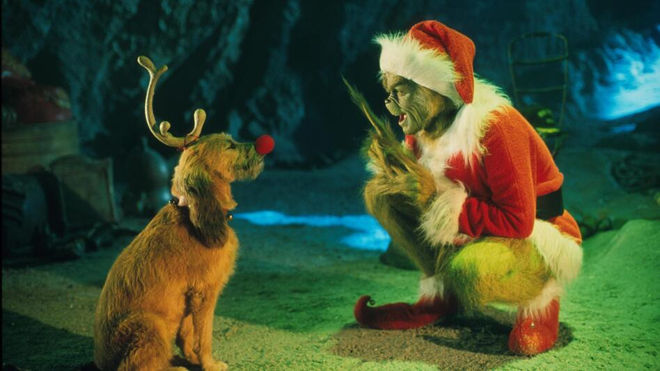 The Grinch, played by Jim Carrey, conspires with his dog Max to deprive the Whos of their favorite holiday in the live-action adaptation <em>Dr. Seuss' How The Grinch Stole Christmas</em>. (Getty Images/Getty Images)