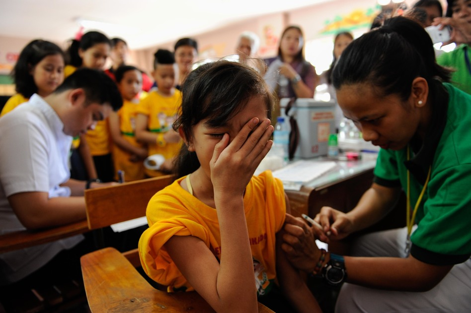 A girl is vaccinated against dengue as part of a public immunization program for children in the Philippines. The program was suspended after the company raised safety concerns about the vaccination.
