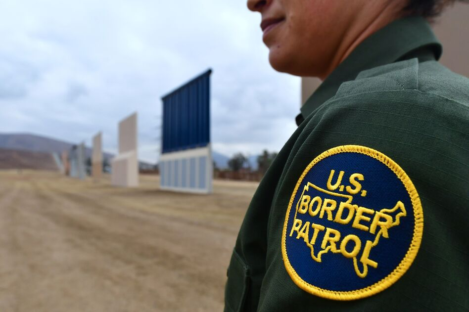A U.S. Border Patrol officer stands near prototypes of President Trump's proposed border wall in San Diego. Border officers apprehended 310,531 people for being in the country illegally in fiscal 2017, a 25 percent decrease from the year before. (Frederic J. Brown/AFP/Getty Images)