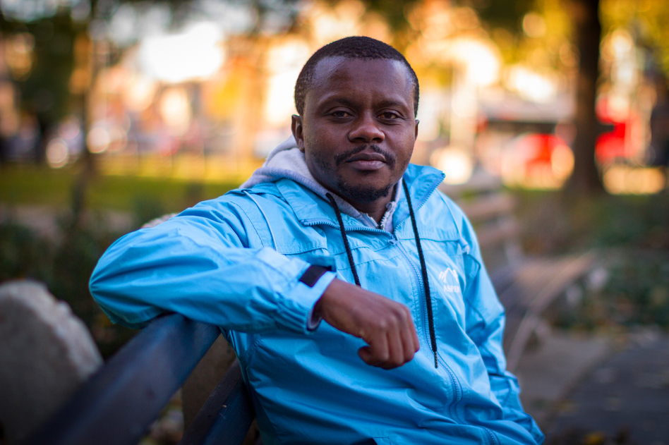 Robert Hakiza, who started a soccer tournament to unite refugees in Africa, sits on a bench in Washington, D.C. (Josh Loock/NPR)