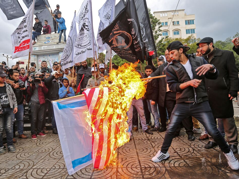 Palestinian protesters burn U.S. and Israeli flags in Gaza City on Wednesday. President Trump has recognized Jerusalem as Israel's capital, upending decades of U.S. policy and ignoring dire warnings from allies. (Mahmud Hams /AFP/Getty Images)