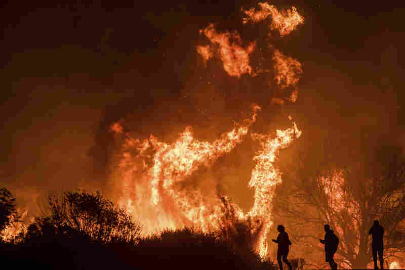 Motorists on Highway 101 watch flames from the Thomas fire leap above the roadway north of Ventura on Wednesday.