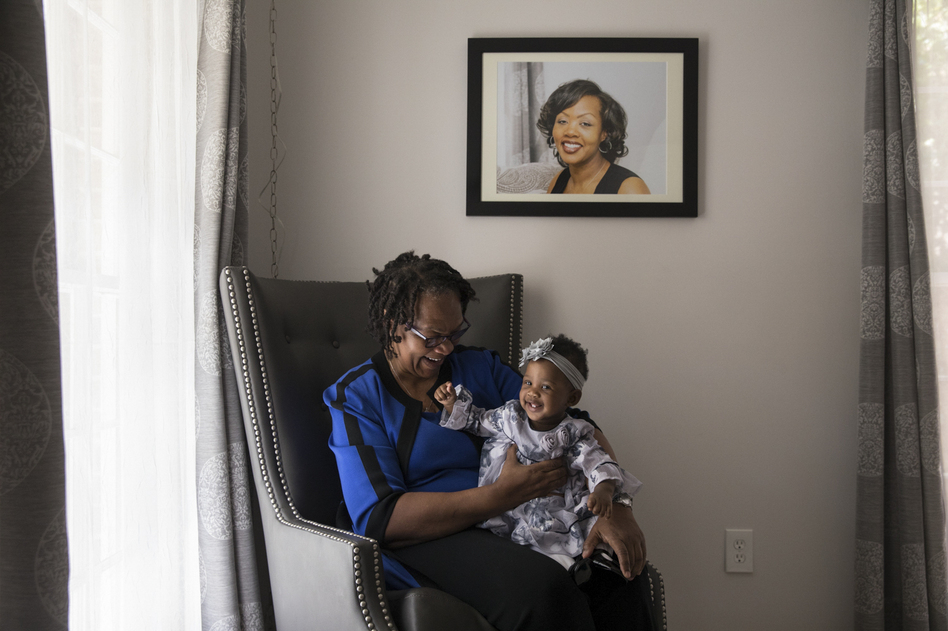 Wanda Irving holds her granddaughter, Soleil, in front of a portrait of Soleil's mother, Shalon, at her home in Sandy Springs, Ga. Wanda is raising Soleil since Shalon died of complications due to hypertension a few weeks after giving birth. (Becky Harlan/NPR)