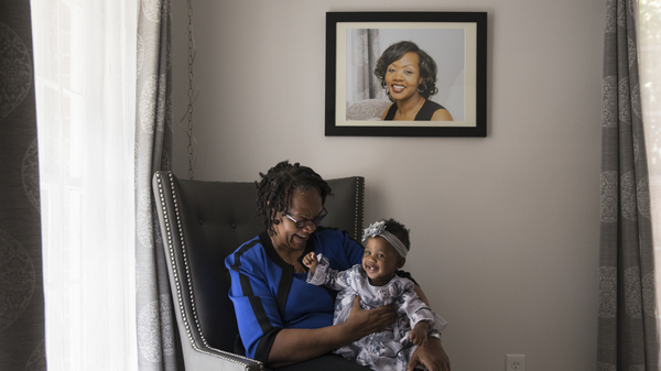 Wanda Irving holds her granddaughter, Soleil, in front of a portrait of Soleil