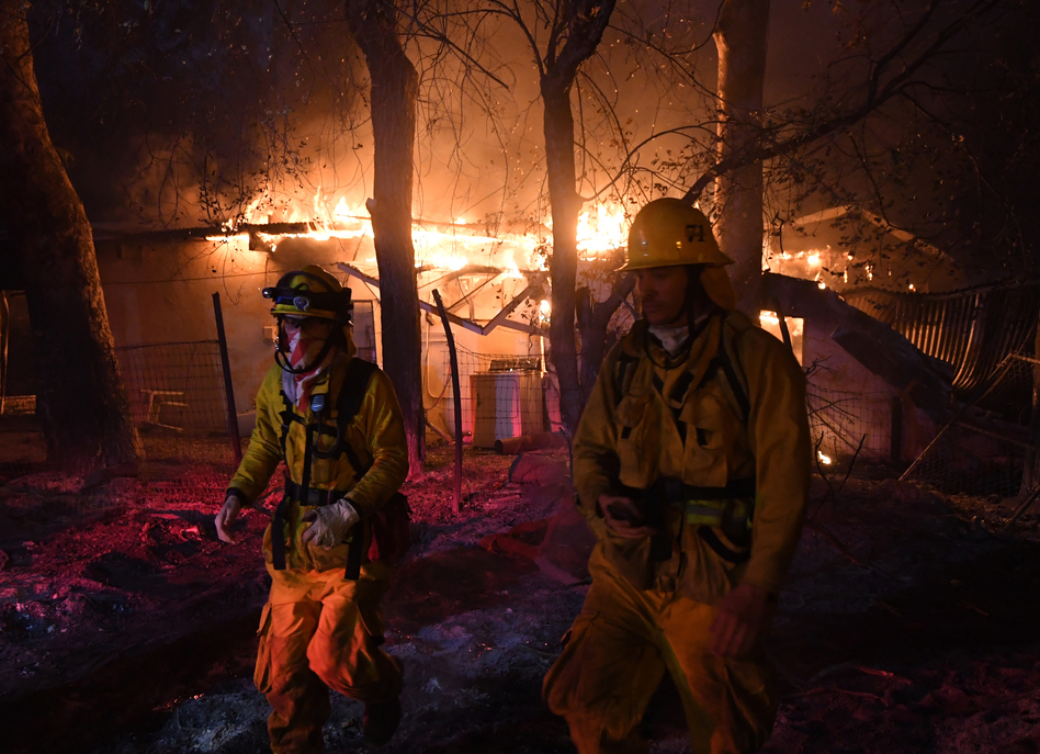 Firefighters step back from a burning house in Carpinteria, Calif., after discovering downed live power lines nearby on Sunday. (Mark Ralston/AFP/Getty Images)