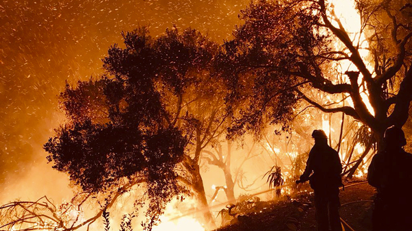 In a photo released by Santa Barbara County Fire Department firefighters knock down flames advancing on homes atop Shepherd Mesa Road in Carpinteria, Calif., on Sunday.