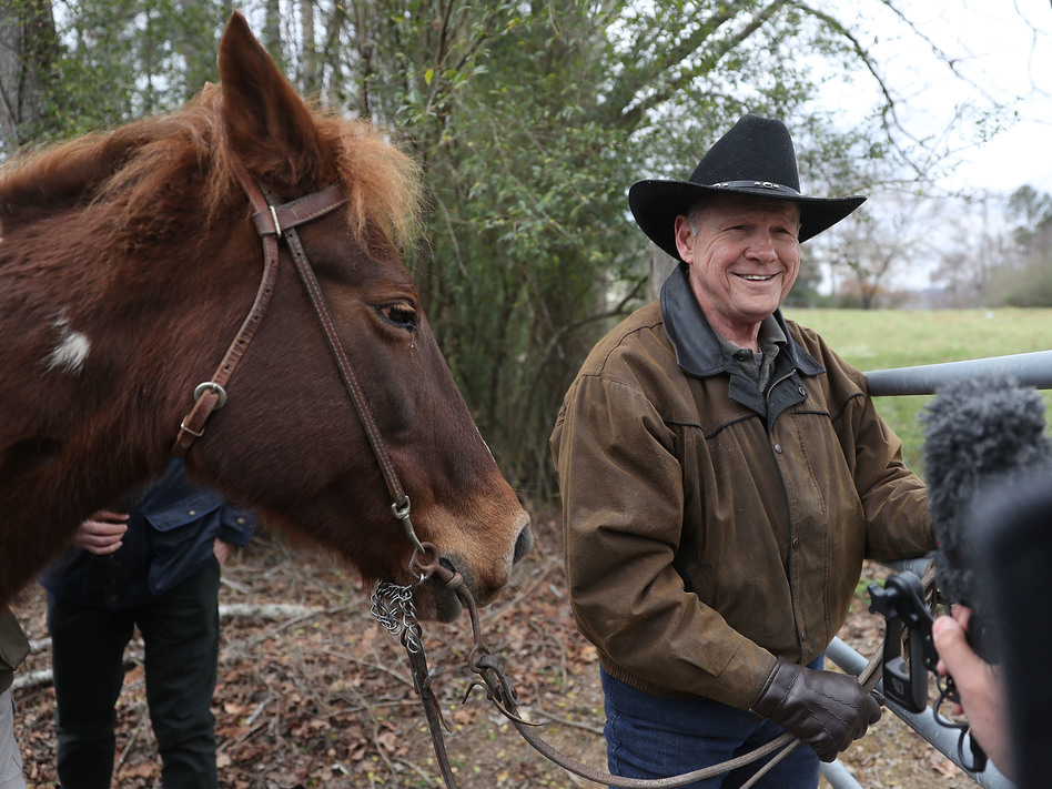 Republican Senate candidate Roy Moore rides in on a horse to vote and is pictured preparing to tie it up. (Joe Raedle/Getty Images)