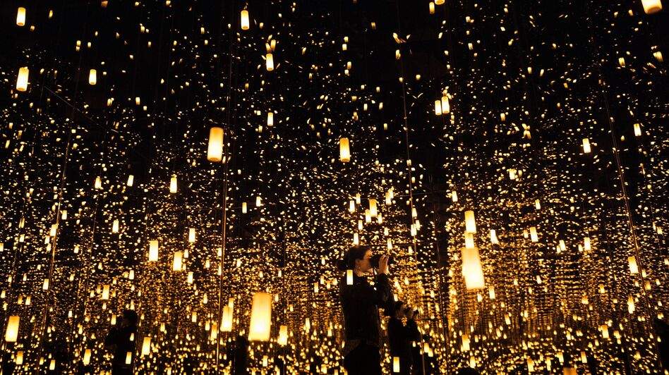 """A woman photographs inside the """"Aftermath of Obliteration of Eternity"""" room during a preview of the Yayoi Kusama's """"Infinity Mirrors"""" exhibit at the Hirshhorn Museum on Feb. 21, 2017 in Washington, D.C. (Brendan Smialowski /AFP/Getty Images)"""