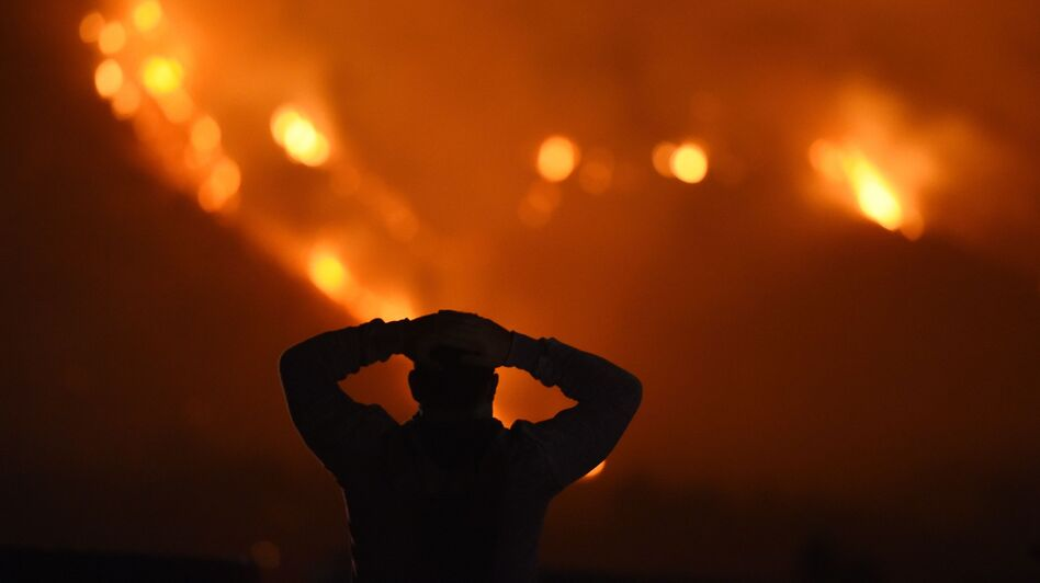 A man watches the Thomas Fire in the hills above Carpinteria, California. (Robyn Beck/AFP/Getty Images)