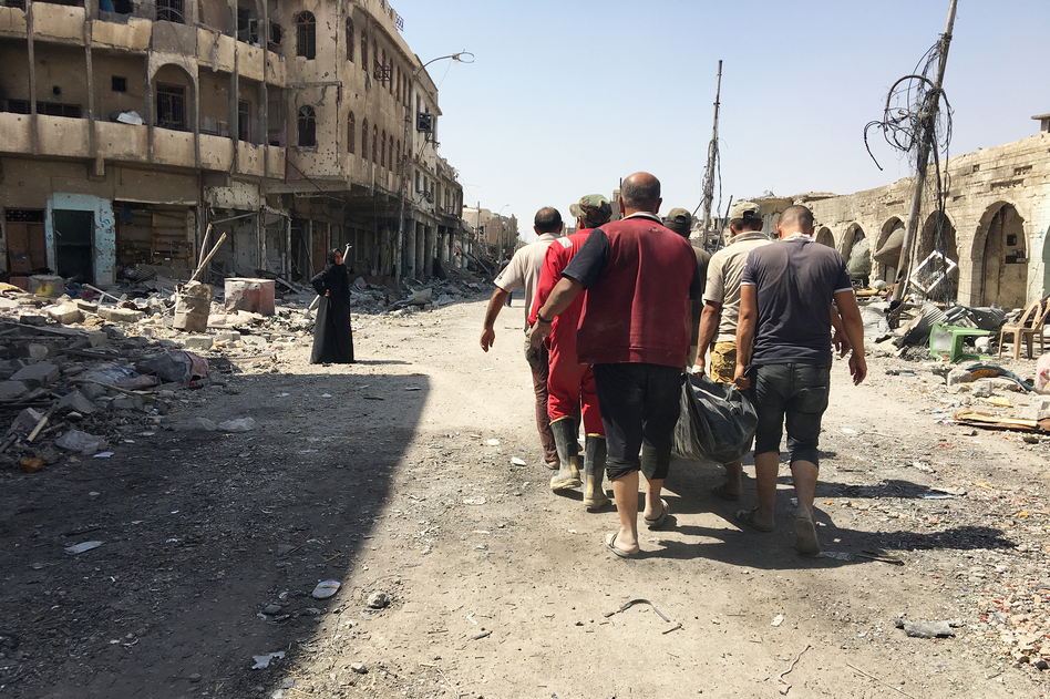 Civil defense workers carrying the body of a civilian retrieved from the rubble of a house destroyed in airstrike. They've collected almost 1,500 bodies so far in west Mosul – many of them women and children – and are still finding casualties. (Jane Arraf/NPR)