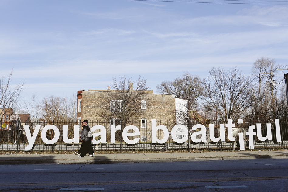 "People are seen walking past the ""You Are Beautiful"" sign, an art installation by Matthew Hoffman, in the Englewood neighborhood on Chicago's South Side. Nearly half of the people in this African-American neighborhood live below the poverty line, and many seniors have no idea there are public services that might help them. (Kristen Norman/NPR)"