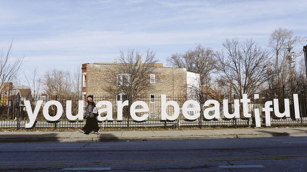 "People are seen walking pass the ""You Are Beautiful"" sign, an art installation, in the Englewood neighborhood on Chicago"