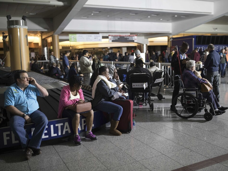 Passengers wait after the lights went out at Hartfield-Jackson Atlanta International Airport on Sunday. Many travelers were stuck in grounded planes for hours. (Branden Camp/AP)