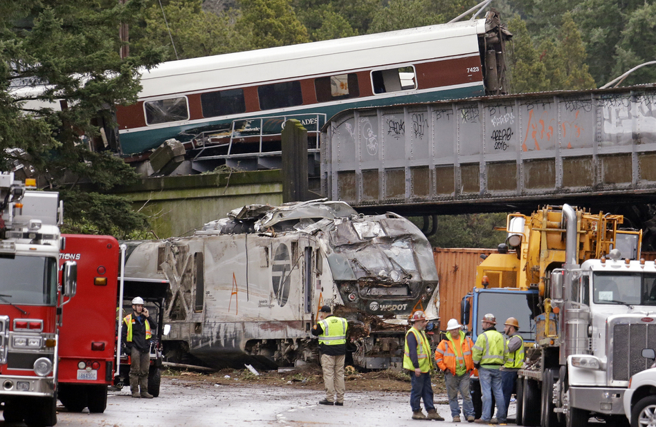 Cars from an Amtrak train lie spilled onto Interstate 5 below as some train cars remain on the tracks above on Monday in DuPont, Wash. (Elaine Thompson/AP)