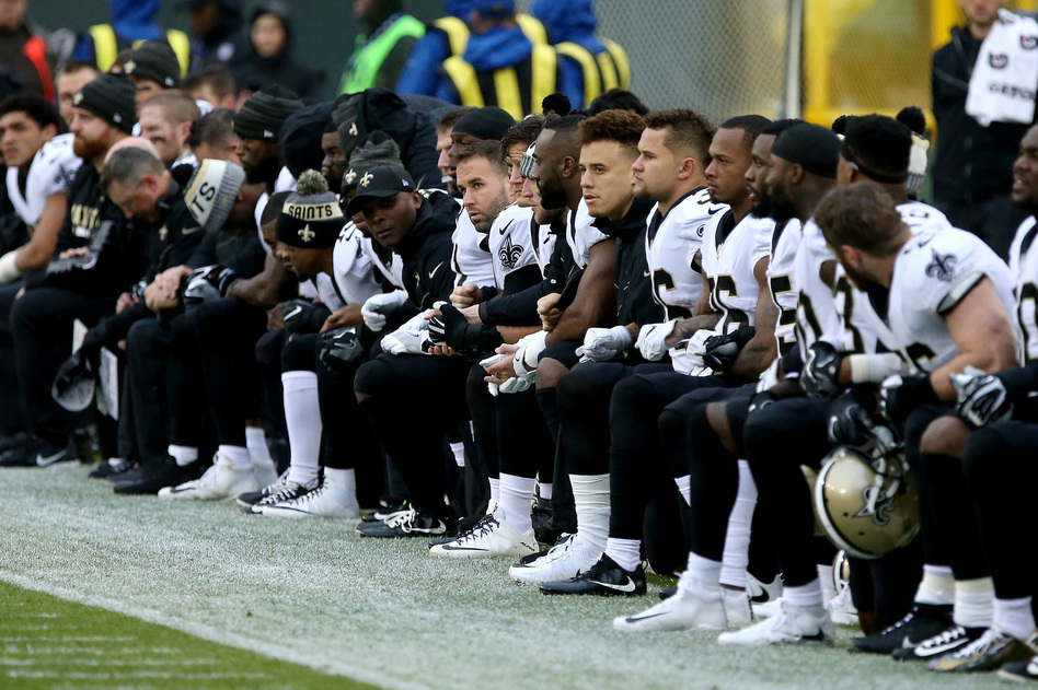 The New Orleans Saints kneel before the playing of the national anthem before the game against the Green Bay Packers at Lambeau Field on Oct. 22. (Dylan Buell/Getty Images)