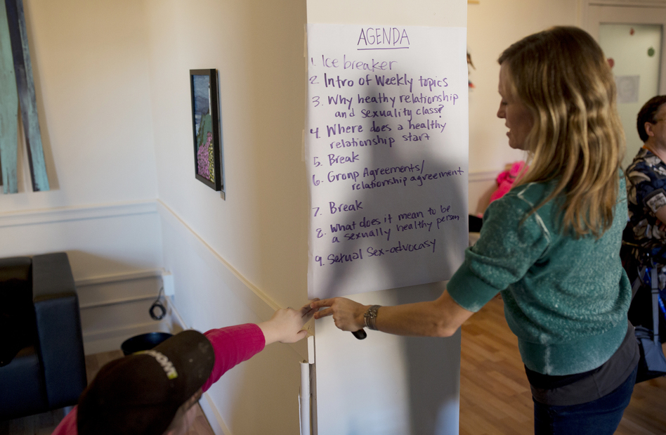 A participant helps Park hang the agenda on the wall at the start of class. (Brianna Soukup for NPR)