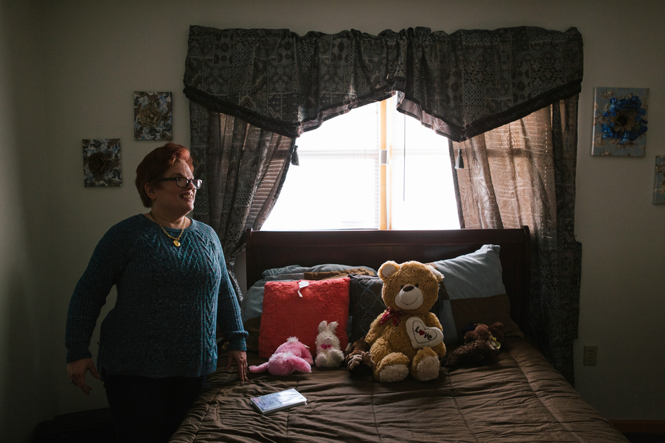 Pauline stands in her room after coming home from a day program for adults with intellectual disabilities. (Michelle Gustafson for NPR)