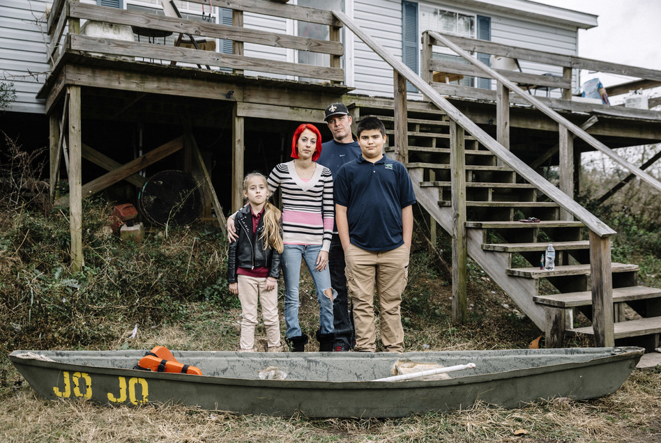 Ollie and Daniel Williams stand in front of their raised home with their children Trinity, 9, and Masen, 12. The land surrounding their house floods so often that the family keeps a small fiberglass canoe tied to the bottom of the front steps and a flat-bottom boat tied to the side of their house to aid in evacuating. (William Widmer for NPR)