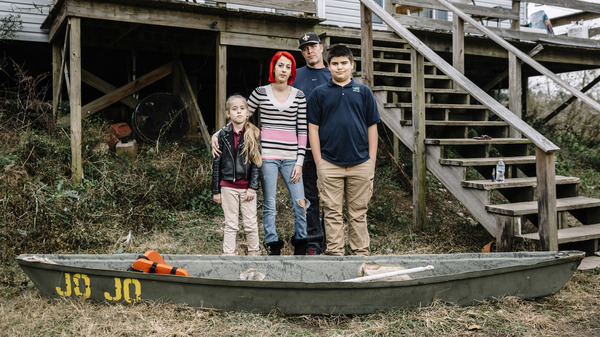 Ollie and Daniel Williams stand in front of their raised home with their children Trinity (9) and Masen (12). The land surrounding their house floods so often that the family keeps a flat-bottom fishing boat called a pirogue tied to the side of their house to aid in evacuating.
