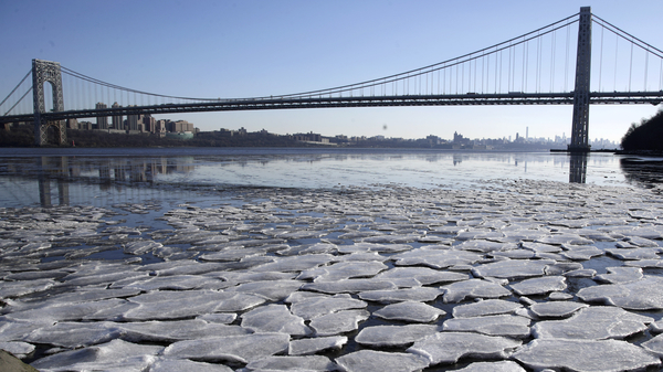 A layer of ice is broken into pieces floating along the banks of the Hudson River at the Palisades Interstate Park with the George Washington Bridge in the background on Tuesday, in Fort Lee, N.J.