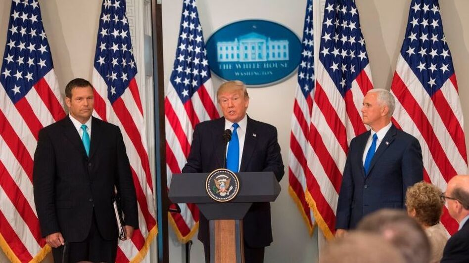 President Trump, flanked by Kansas Secretary of State Kris Kobach and Vice President Pence, speaks during the first meeting of his Presidential Advisory Commission on Election Integrity in July. (Saul Loeb/AFP/Getty Images)