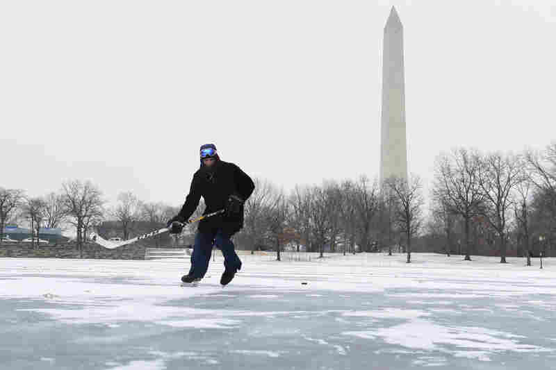 Fabian Olaya plays hockey on a pond near the Washington Monument in Washington, D.C.
