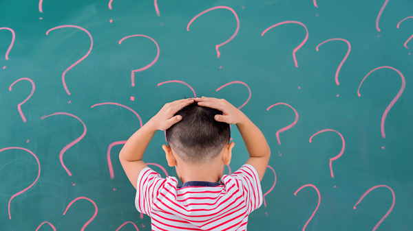 Little boy in front of blackboard with question marks.