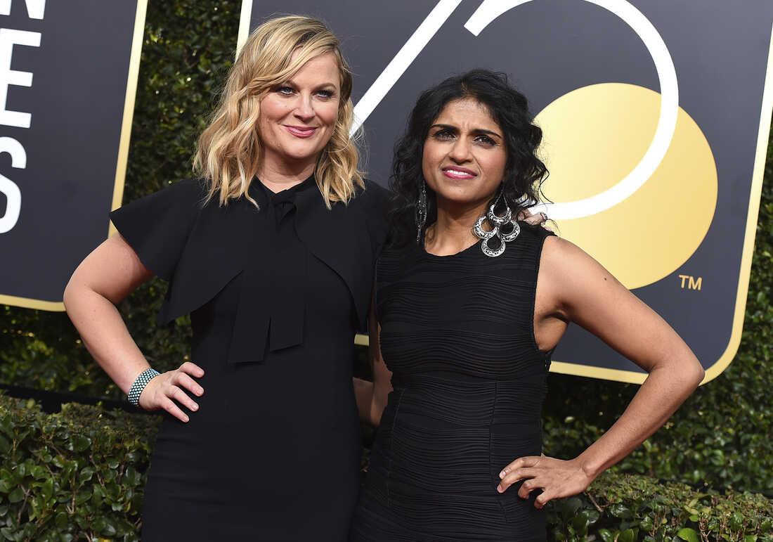 Amy Poehler, left, and Saru Jayaraman arrive at the 75th annual Golden Globe Awards.