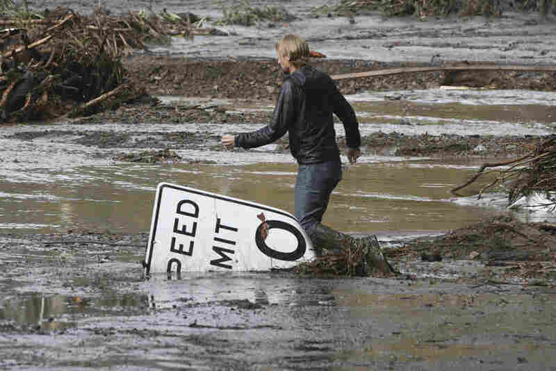 Phillip Harnsberger crosses through mud from a flooded creek on Sheffield Drive in Montecito Calif