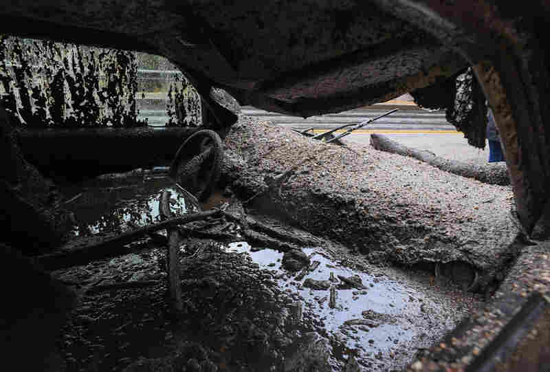 Mud fills the interior of a car destroyed in a rain-driven mudslide in a neighborhood under mandatory evacuation in Burbank