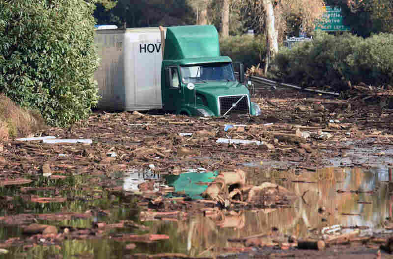 A semitractor-trailer sits stuck in mud on U.S. Highway 101, in Montecito.