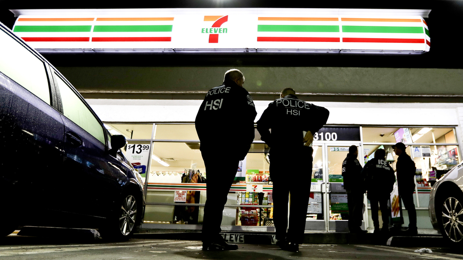 ICE agents serve an employment audit notice at a 7-Eleven in Los Angeles Wednesday. Agents raided 98 stores across the country. (Chris Carlson/AP)