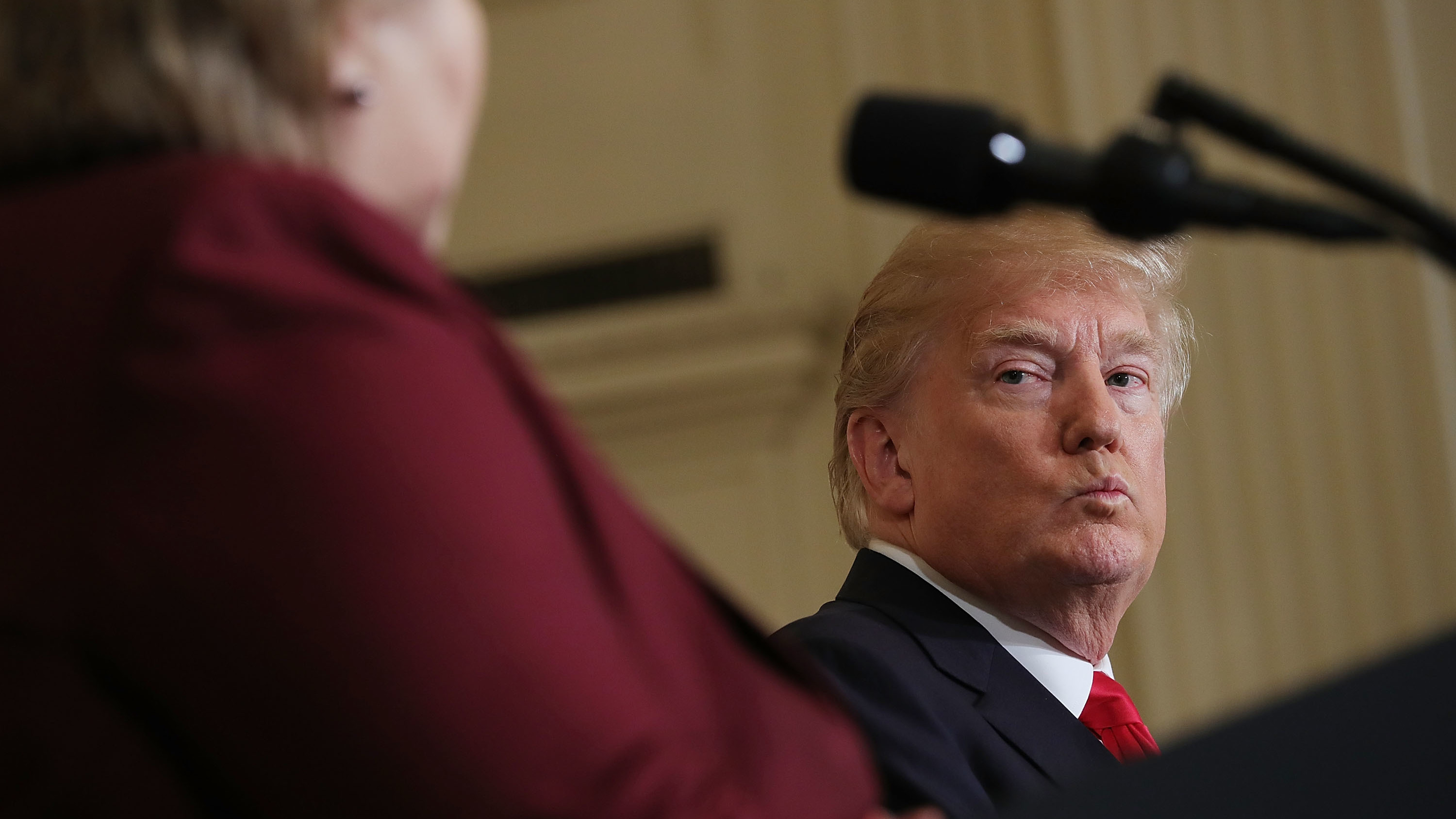 """President Trump listens as Norwegian Prime Minister Erna Solberg speaks at a joint news conference Wednesday. At an Oval Office meeting on immigration policy, Trump said the U.S. should want more people from countries like Norway, disparaging Haiti and what he called """"shithole countries"""" in Africa."""