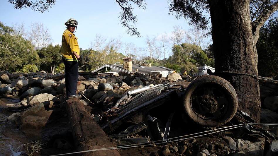 A firefighter searches for people trapped in mudslide debris on Jan. 10 in Montecito, Calif.
