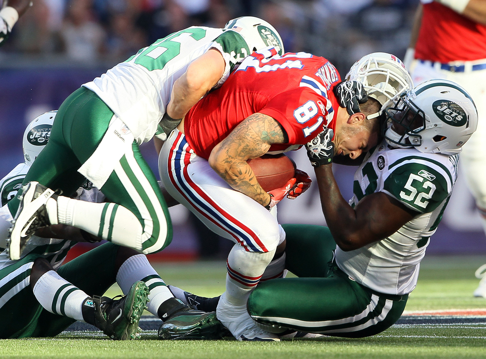 Aaron Hernandez (81), of the New England Patriots, lost his helmet during this play against the New York Jets in 2011. Hernandez killed himself in 2017, and researchers found that he had had one of the most severe cases of CTE ever seen in someone his age. (Elsa/Getty Images)