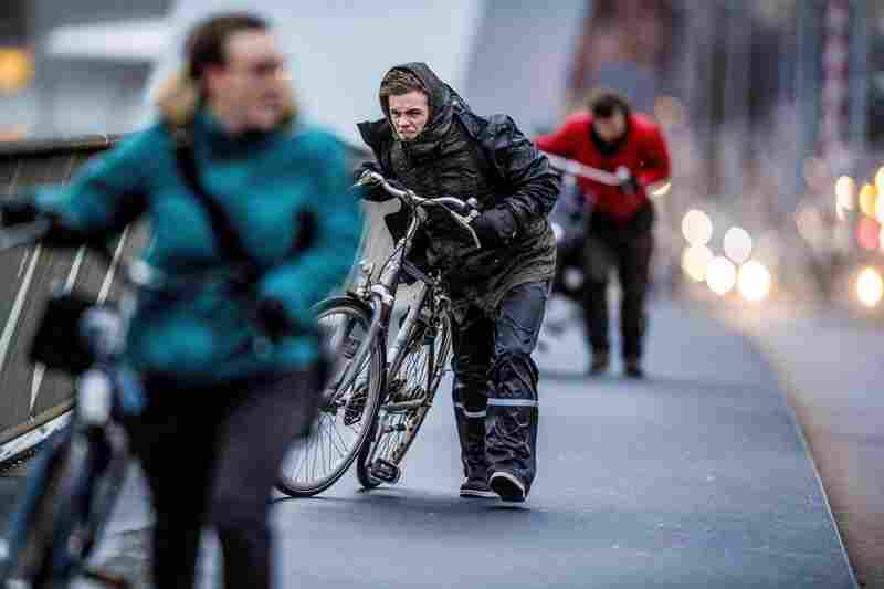 People walk their bicycles through fierce winds in Rotterdam, Netherlands, on Thursday.