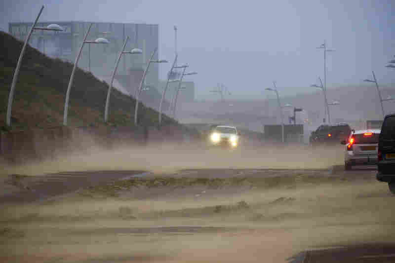 Sand blows across a road as hurricane-force winds sweep through The Hague.