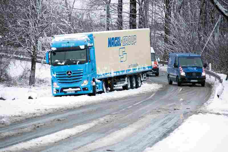 A truck is stuck on the side of a snow-covered road in northern Germany. Five people, including two fire fighters, were killed in the storm.
