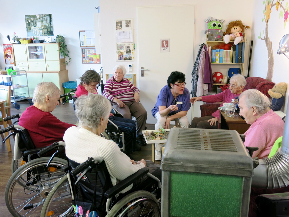 "Caretaker Sylvana Tyralla conducts a memory exercise with AlexA nursing home residents in one of two former East German ""remembrance rooms."" (Soraya Sarhaddi Nelson/NPR)"